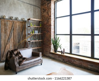 brutal interior in a dark brown color with a leather sofa and large window. Loft style room