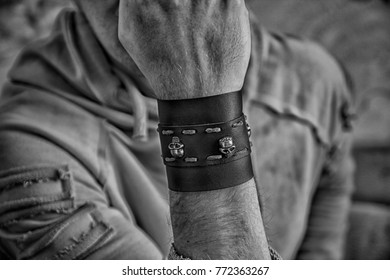Brutal leather rock or gothic wristband or bracelet with metall skulls on man hand