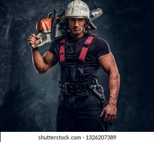 Brutal logger wearing protective clothes and helmet posing with a chainsaw on his shoulder and looking at a camera