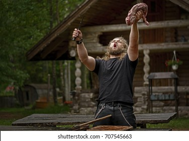 Brutal long hair man wearing leather pants and chains prepare meat near forest house. like a sacrifice