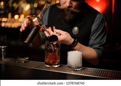 Brutal male bartender pouring an alcohol cocktail with metal jigger