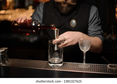 Brutal male bartender pours alcohol drink with metal jigger, two glasses standing on metal bar counter
