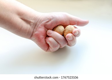 A brutal male hand holds walnuts in its fist and tries to crack them. Indoors on a white background, close-up, copy paste selective focus
