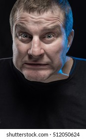 Brutal man actor gesticulates and grimaces on a black background. Caricature change.
