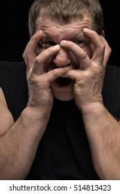 Brutal man actor grimacing on a black background. Caricature change.