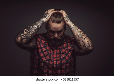 Brutal man with beard holding his head with tattooed arms and looking down. Isolated on grey background.