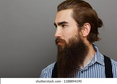 Brutal man with a beard looks away.Man is dressed in a blue shirt with lines
