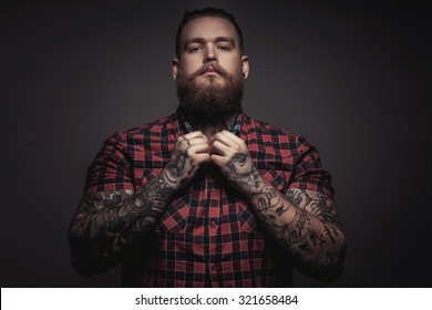 Brutal man with beard and tattoes on his arms. Isolated on grey background.