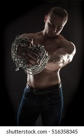 Brutal man bodybuilder athlete with a chain in his hands on a black background.