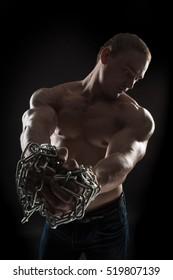 brutal man bodybuilder athlete holding a chain on a black background