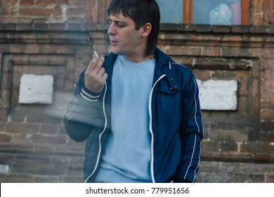 brutal man brunette walks the abandoned Park. emotional portrait. long hair and problematic skin: acne and red spots. street style: jeans and jacket. actively smokes about houses