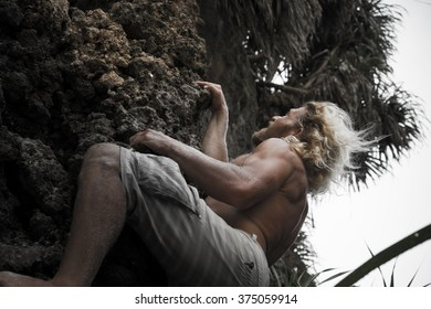 brutal man climbing up the rock . Blonde with long hair to conquer the peak .