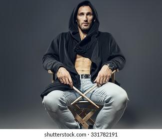 Brutal man in a hood with drumsticks
