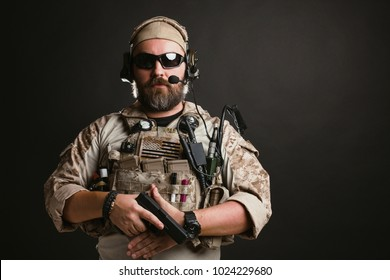 Brutal man in the military desert uniform and body armor stands and holds a gun on a black background in the Studio. The bearded player in the airsoft safety glasses or goggles and active headphones.