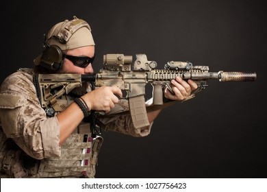 Brutal man in the military desert uniform and body armor stands in a fighting rack and holds his rifle on a black background. The bearded player in the airsoft safety glasses aiming a rifle.