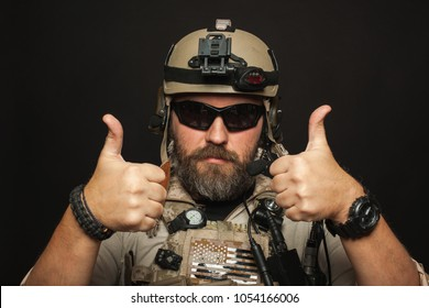 Brutal man in military desert uniform and body armor shows two fingers up on black background in Studio. The bearded player in the airsoft safety glasses or goggles and active headphones.