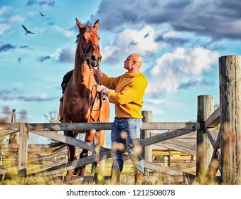 brutal man in a mustard sweater with a panicked horse in a field
