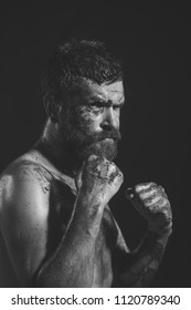 brutal man is ready for fight. Power, might, magic. Man in fight position with blood paint on face, fists. Bearded hipster with tattoo on chest skin on black background. Sport, boxing, fighting.