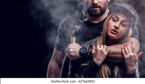 Brutal man and sexy woman are vaping. Studio shooting. Black background.