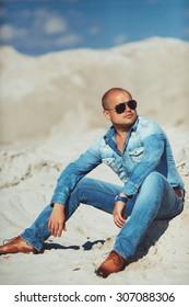 brutal man sitting on the sand, bronzed