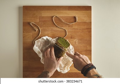 Brutal man tattooed hands cut healthy spinach home made green rustic bread with vintage knife on slices. Wooden board white table top view