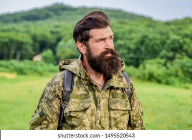 Brutal manly guy. Hike and travel. Weekend leisure and vacation. Hiker bearded man hiking. Hiker ready for adventures. Man bearded backpacker wear camouflage jacket nature background. Hiker tourist.
