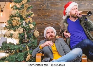 Brutal men celebrate new year near christmas tree. Bad habits to kick before the end of year. Get rid of harmful habits. How to break bad habits. Men drink champagne and smoking. New years resolution.