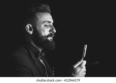 Brutal and modern fashion male hairdresser with scissors and a razor in his hands.  Fashionable barber in a suit