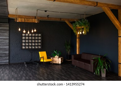 Brutal modern interior in a dark color with a leather sofa. Loft style living room