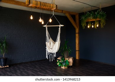 Brutal modern interior in a dark color with hammock. Loft style living room