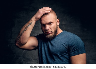 A brutal muscular male dressed in a blue t shirt touch his head.