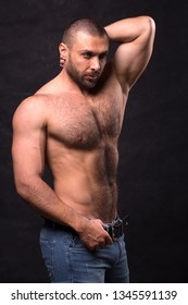 Brutal muscular man, in jeans. Tioless bodybuilder posing standing over dark background.