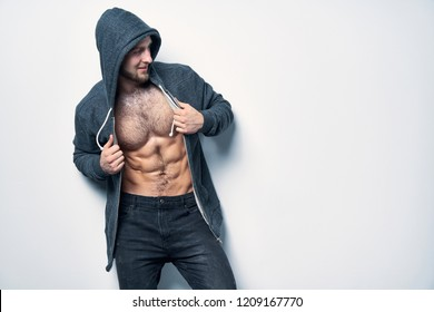 Brutal naked muscular man dressed in a grey hoodie posing by white wall looking smiling to side at blank copy space