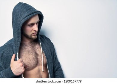 Brutal naked muscular man dressed in a grey hoodie posing by white wall looking to side at blank copy space