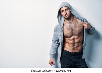 Brutal naked muscular man dressed in a grey hoodie posing by white wall, looking at camera