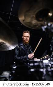 brutal portrait of a man musician with a beard and in black clothes on the background of musical instruments drums