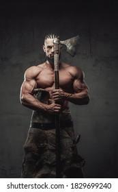 Brutaler und mächtiger viktierender Krieger mit Schrecken und Bart posiert mit Axt, die die Hälfte seines Gesichts auf dunklem Hintergrund bedeckt.