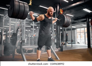 Brutal rude man powerlifter standing in the middle of big brightly lighted gym room, holding barbell, trying to raise above head, expressing power and strength, indoor shot