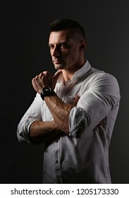 Brutal serious business man thinking in white style shirt on grey dark shadow background. Closeup portrait.
