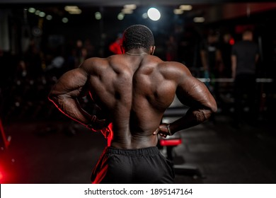 Brutal strong athletic man pumping up muscles. Doing workout on sport equipment - muscular bodybuilder doing exercises in gym with naked torso. Fitness and bodybuilding concept. View from the back.
