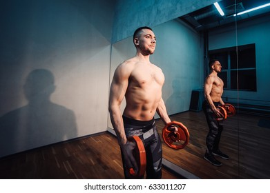 Brutal strong athletic man pumping up muscles and train in gym workout bodybuilding concept background - muscular bodybuilder men doing exercises in gym naked torso. with the mirrow