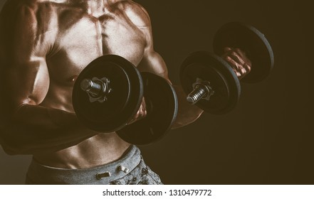 Brutal strong athletic men doing exercises with dumbbell over empty background.  Bodybuilding  and healty life concept. Toned Image