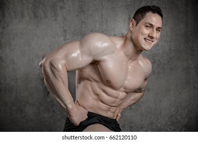 Brutal strong athletic men pumping up muscles workout bodybuilding concept grey background muscular bodybuilder handsome men doing exercises in gym naked torso fitness and bodybuilding workout concept