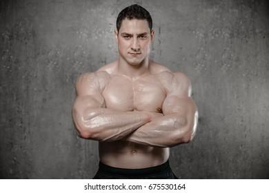 Brutal strong athletic men pumping up muscles workout bodybuilding concept grey background - muscular bodybuilder handsome men doing exercises in gym naked torso fitness and bodybuilding workout