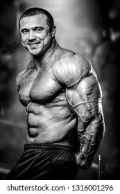 Brutal strong athletic muscular men pumping up muscles workout bodybuilding concept background - muscular bodybuilder handsome men doing exercises in gym naked torso