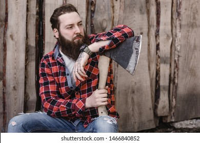 Brutal strong man with a beard dressed in a checked shirt and torn jeans is sitting with an ax in the hands against the background of a wooden fence