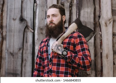 Brutal strong man with a beard dressed in a checked shirt standing with an ax in the hands against the background of a wooden fence