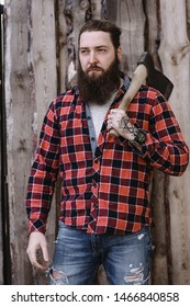 Brutal strong man with a beard dressed in a checked shirt and torn jeans standing with an ax in the hands against the background of a wooden fence