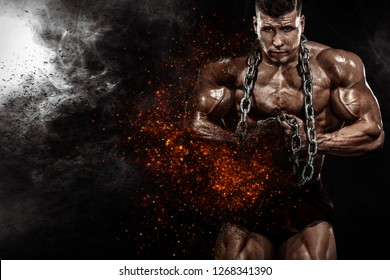 Brutal strong muscular bodybuilder athletic man pumping up muscles with chains on black background. Workout bodybuilding concept. Copy space for sport nutrition ads.
