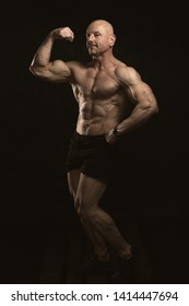 Brutal strong muscular bodybuilder athletic man pumping up muscles with dumbbell on black background